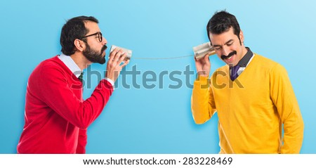 Twin brothers talking through a tin phone over colorful background - stock photo