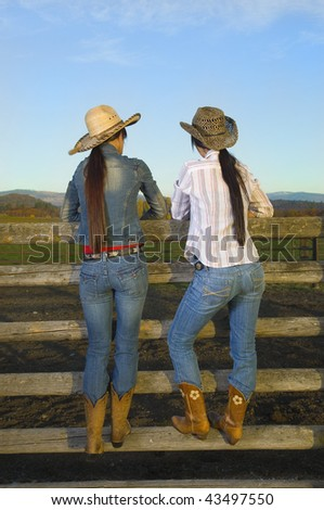 Twin Cowgirls at sunset leaning against a wood fence - stock photo