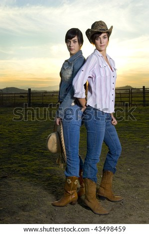 Twin cowgirls in a coral against a fall sunset - stock photo