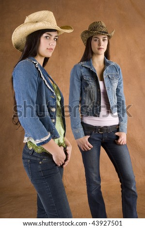 Twin cowgirls wearing jean jackets with straw hats - stock photo