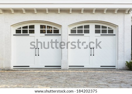 Twin double garage doors to a white home. Twin set of double swinging garage doors to a white, brick family home. The doors have glass window detail and door handles. Also seen is the   - stock photo