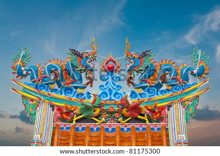 Twin dragon statues in Chinese style on top of general temple roof with blue sky - stock photo