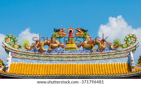 Twin Dragons Statue on Chinese temple roof with blue sky and white clouds