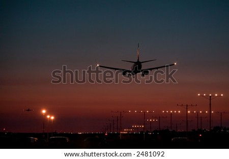 Twin engine passenger jet coming in for a landing during dusk, while another takes off in the distance