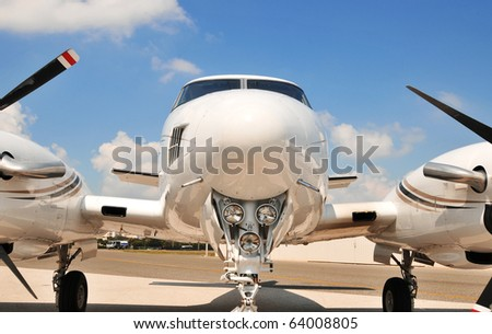 Twin engine plane on the tarmac for scheduled maintenance. The nose end and lights are the focal point of this speedy corporate plane. The props, engines and landing gear are partially visible.
