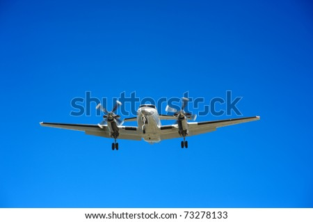 Twin engine propeller airplane approaching for landing - stock photo