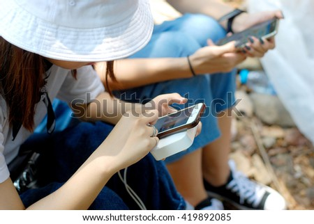 Twin girl looking at her telephone in the forest - Asian people