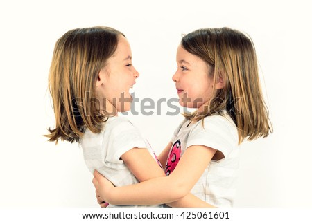 Twin girls are looking at each other and smiling. Concept of family and sisterly love. Profile side view of sisters playing. - stock photo