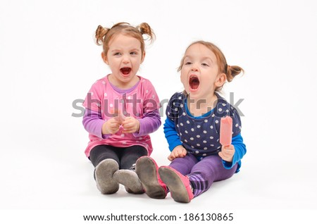 Twin girls eating ice cream and screaming - stock photo