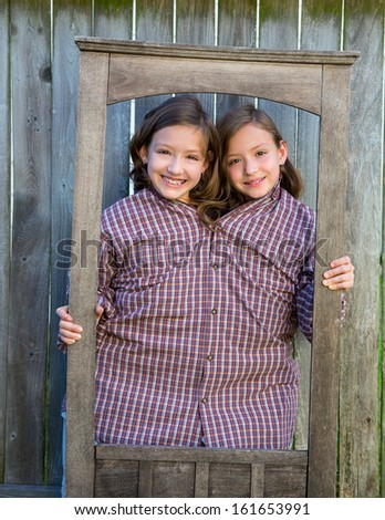 twin girls fancy dressed up pretending be siamese with dad shirt playing with grunge border frame - stock photo
