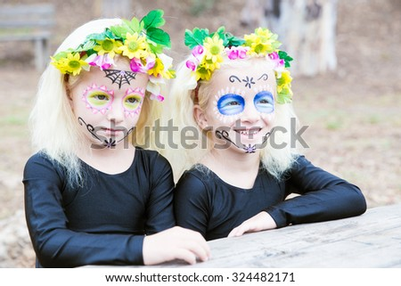 Twin girls in black clothing with sugar skull makeup smiling - stock photo