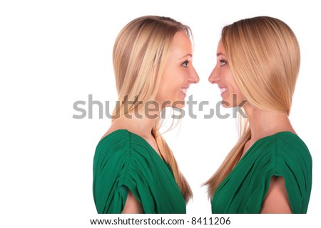 Twin girls smiling face-to-face - stock photo