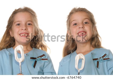 twin girls with cake beaters - stock photo