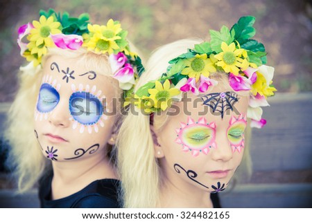 Twin girls with closed eyes in halloween costume outdoors - stock photo