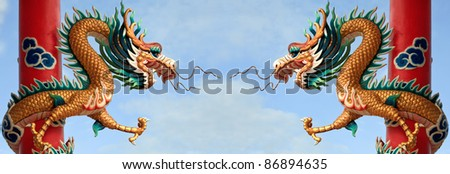 Twin Golden Chinese Dragon Wrapped around red pole on blue sky