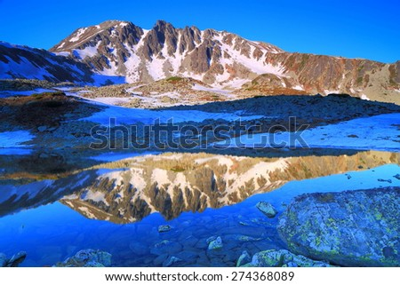 Twin image of a distant mountain reflected by glacier lake at sunrise - stock photo