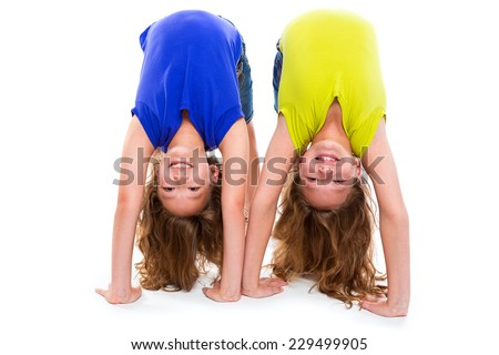 twin kid sisters playing as flexible contortionist happy on white background - stock photo