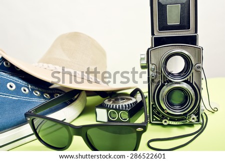 twin-lens reflex camera with sneaker and sunglasses - stock photo