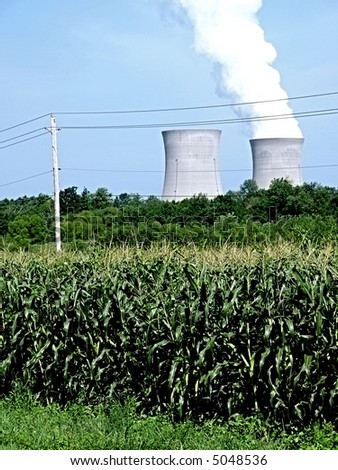 Twin nuclear power stacks rise above a corn field, showing the difference between the two power options - stock photo