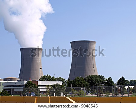 Twin nuclear power stacks rise above an office building into a clear blue sky - stock photo