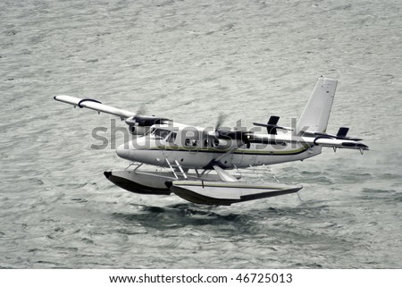 twin propeller engine hydroplan taking off from water surface - stock photo