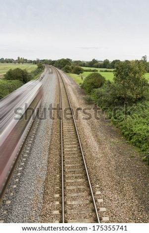 Twin railway tracks curving to the left, UK standard gauge, train moving away at speed (blurred). - stock photo