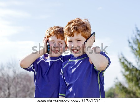Twin redhead brothers talking on cellphones - stock photo