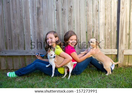 Twin sister girls playing with smartphone and chihuahua dog sitting on backyard - stock photo