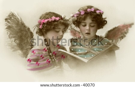 Twin sisters, dressed as singing angels - an early 1900s hand-tinted vintage photograph - stock photo
