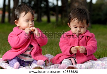 Twin sisters eating outdoors - stock photo