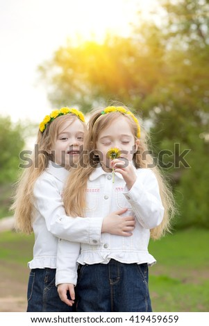 Twin sisters having embraced smell yellow dandelions - stock photo