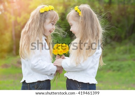 Twin sisters keep the big bouquet of yellow  dandelions in spring park - stock photo