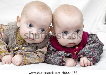 Twin sisters lying down focusing their attention. - stock photo