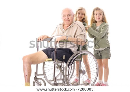 twin sisters pushing eldery man in wheelchair - stock photo