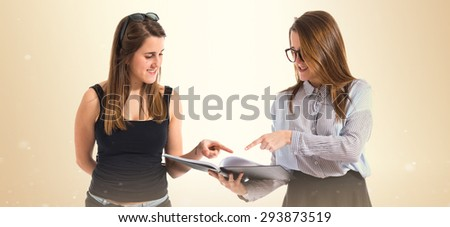 Twin sisters showing a book over ocher background