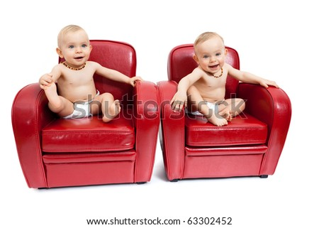 Twin sisters sitting on  red armchairs. - stock photo