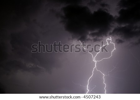 Twin strokes of lightning that splits in two half way through the stroke - stock photo