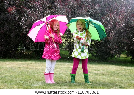 twin young girls playing in rain with coats, umbrellas and boots - stock photo