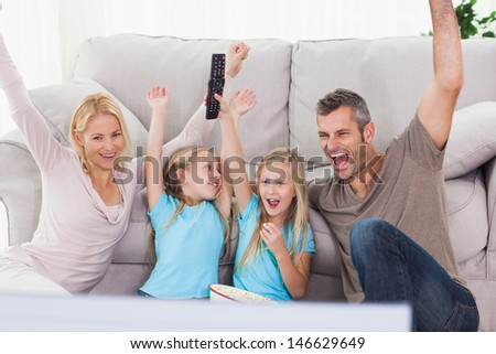 Twins and parents raising arms while watching television sitting on a carpet - stock photo