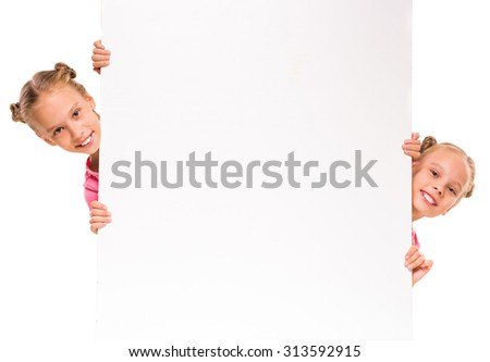 Twins girls are showing blank signboard or copyspace for slogan or text, isolated over white background. - stock photo