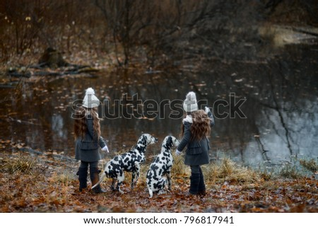 Twins girls walking with their Dalmatian dogs in rainy autumn park