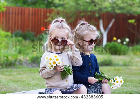 twins girls with bunches of daisies - stock photo