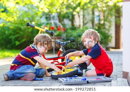 Twins, little boys repairing broken bike, outdoors. - stock photo