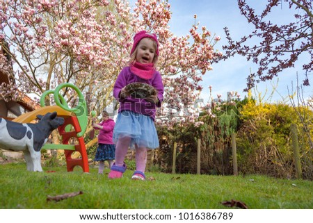 twins playing in the backyard with a blooming magnolia tree in the background