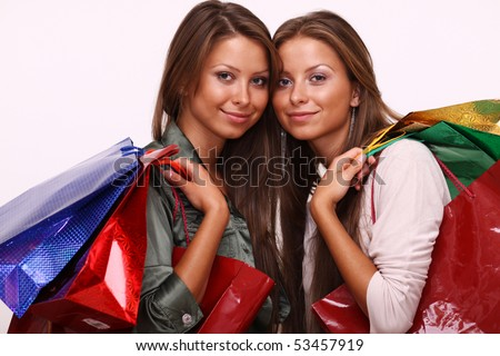 Twins sisters holding shopping bags on white isolated - stock photo