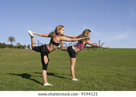 twins stretching in the park - stock photo