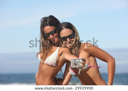 twins taking a photo of themselves on the beach - stock photo