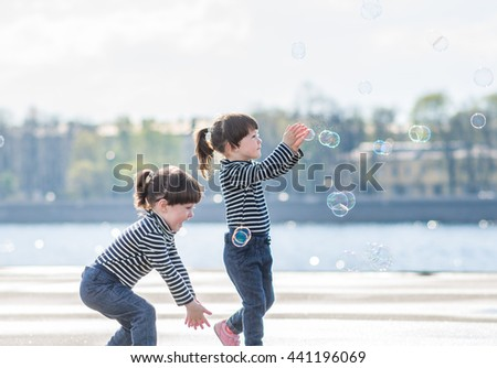 twins trying to catch soap bubble - stock photo