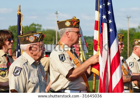 TWINSBURG, OH - June 5: A color guard marches past at the beginning of Relay for Life, an annual fundraising event sponsored by the American Cancer Society, June 5, 2009, in Twinsburg, Ohio. - stock photo