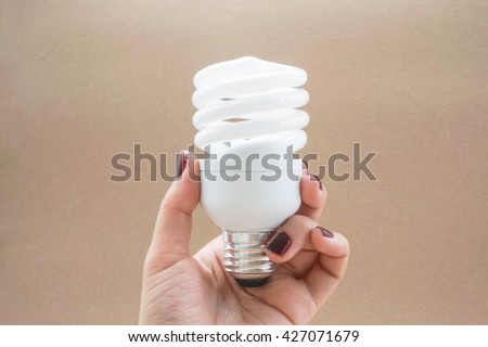 Twist LED light bulb with screw base in palm with brown background